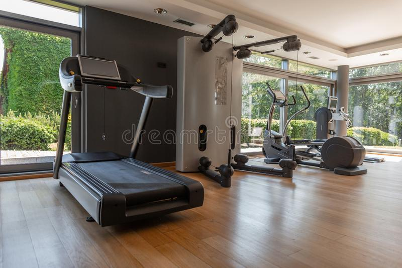Moderne gymnastiek met panoramische vensters Sportuitrusting in de sportenruimte Verschillende simulators en tredmolens binnen stock afbeelding