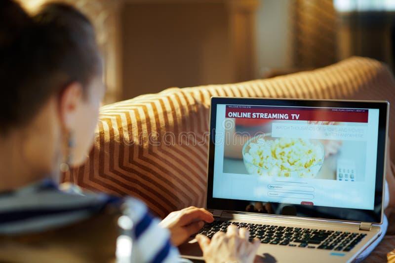 Moderne Hausfrau, die Internet-Fernsehen verwendet lizenzfreie stockfotos