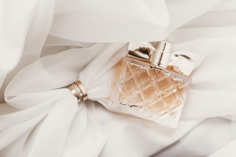Moderne heiratende goldene Ringe und stilvolle Parfümflasche auf weichem f stockfotografie
