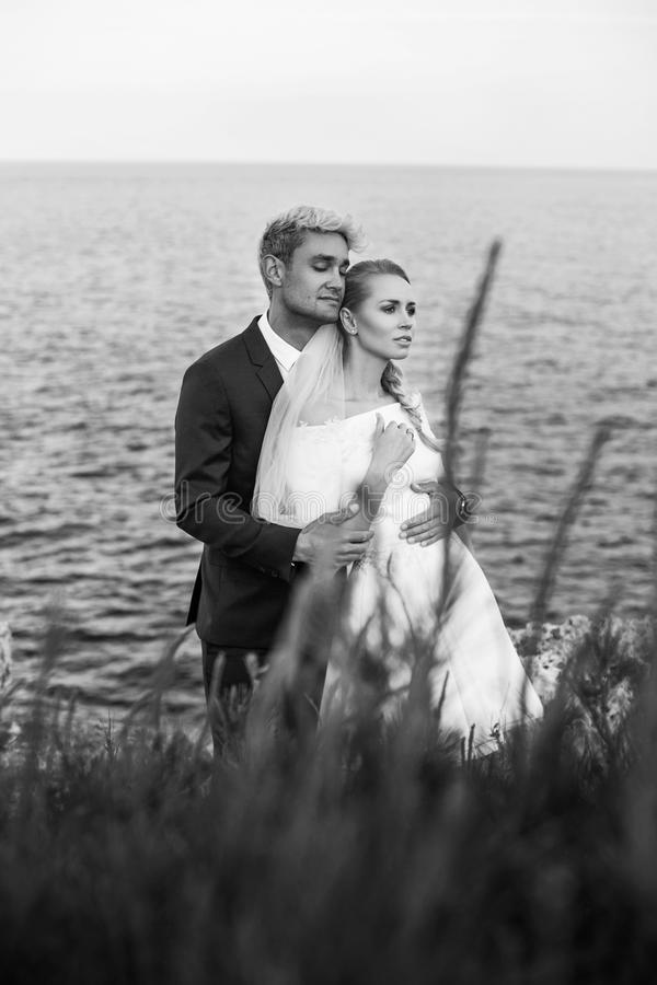 Moderne Hochzeitspaare Braut und Bräutigam Mädchen versteckt sich im Hemd eines Mannes Im Freienportrait stockfotos