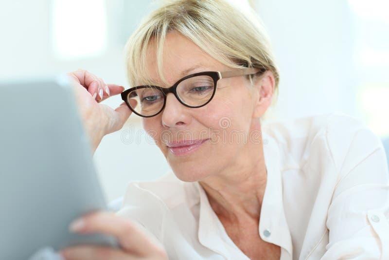 Moderne hogere die vrouw met oogglazen met wifi worden verbonden stock afbeelding
