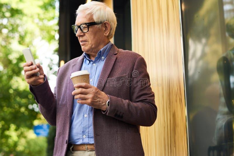 Moderne Hogere Mens met Smartphone stock afbeeldingen