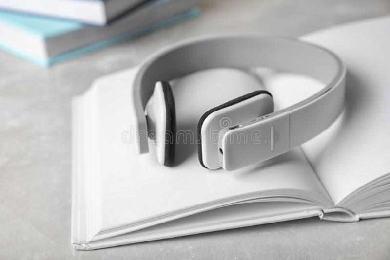 Moderne hoofdtelefoons met hardcoverboek op grijze achtergrond stock foto