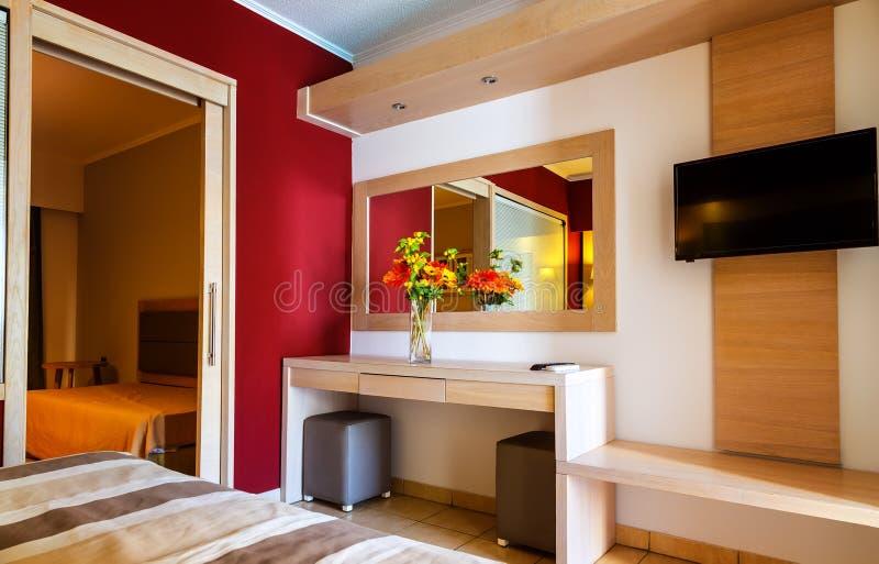 Moderne Hotelzimmerinnenraumluxusdetails Spiegel und Vase Blumen auf Tabelle lizenzfreies stockfoto