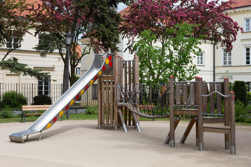 Moderne houten en metaalspeelplaats met schuif en het schudden brug voor kinderen stock foto