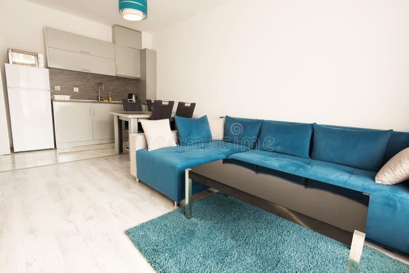Moderne Innenarchitektur des hellen und gemütlichen Wohnzimmers mit Sofa, Speisetische und Küche Grau- und Türkisblaustudiowohnun stockbild