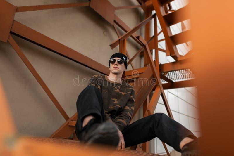 Moderne jonge hipstermens in zwarte hoed in jeans in in zonnebril in groen militair overhemd in leertennisschoenen het rusten stock fotografie