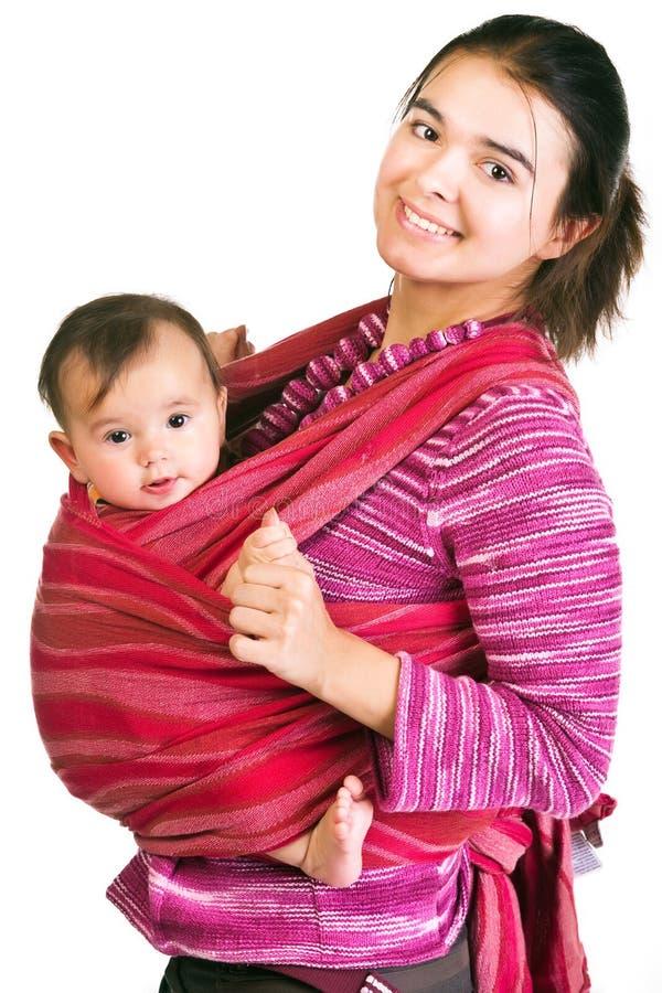 Moderne jonge moeder dragende baby in een slinger royalty-vrije stock afbeelding