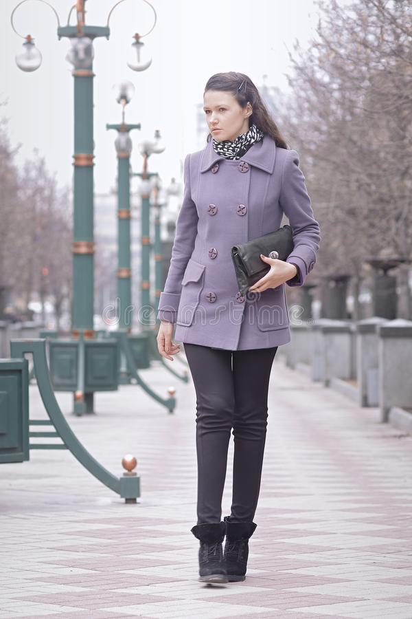 Moderne jonge vrouw die op stadsstraat lopen op de herfstdag stock fotografie