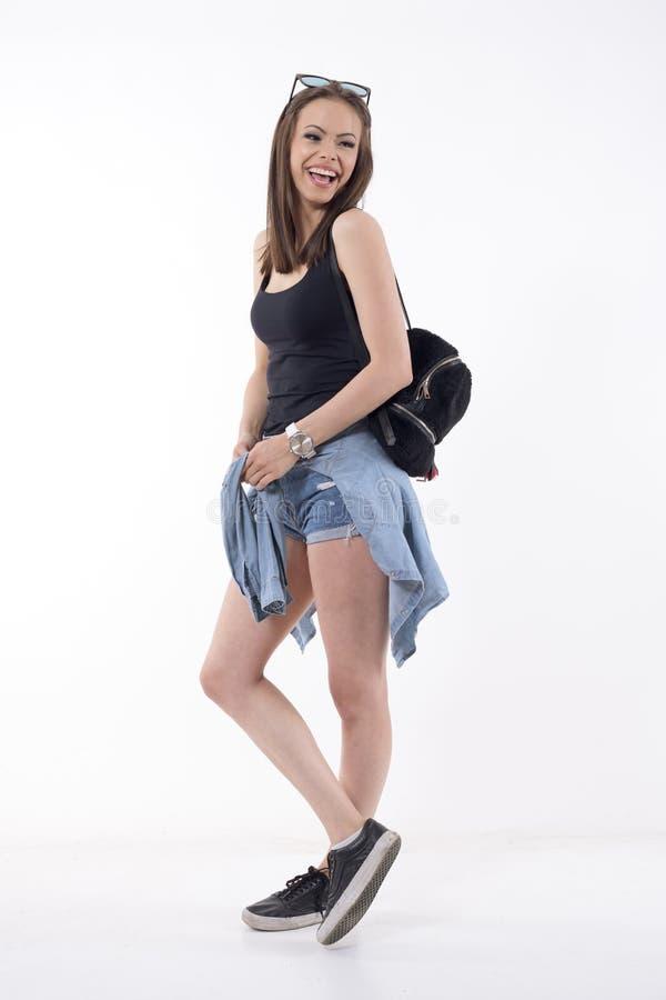 Moderne Jugendliche in der kurzen Jeanshose mit der zurück schauenden und lachenden Plüschtasche stockfotografie