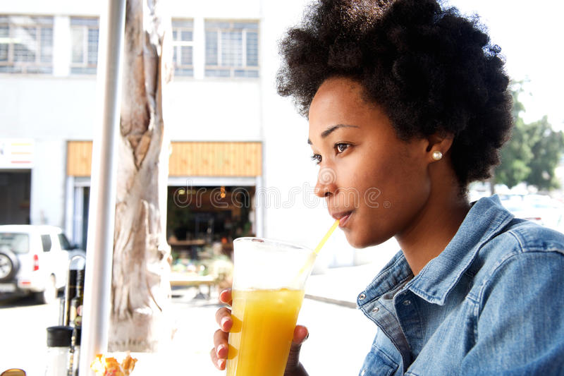 Moderne junge afrikanische Frau, die an Orangensaft nippt lizenzfreie stockbilder