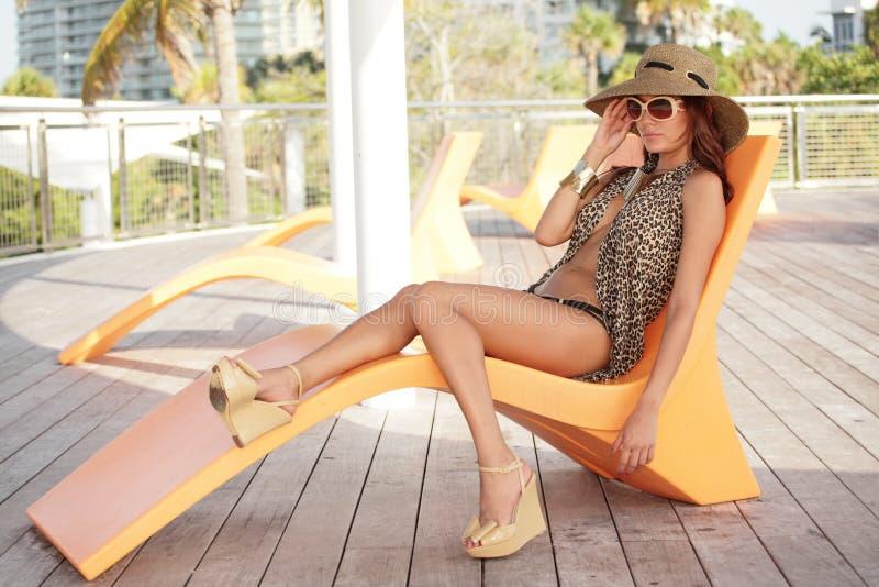 Moderne junge Frau auf einem Aufenthaltsraumstuhl lizenzfreie stockfotografie
