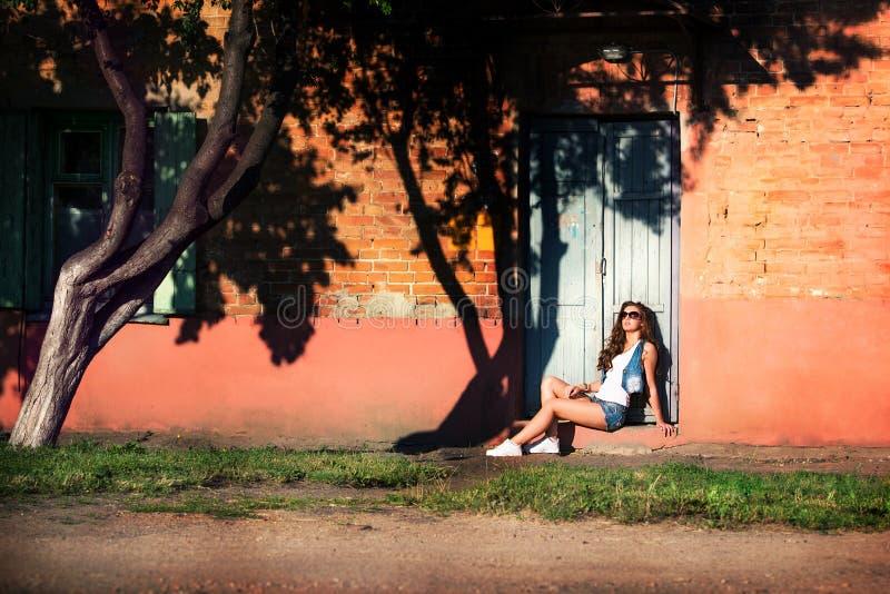Moderne junge Frau in den sexy Denimkurzen hosen und -Sonnenbrille Winkel des Leistungshebels stockfotos