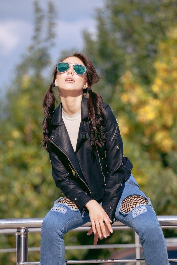 Moderne junge Frau in der Felsenartkleidung, schwarze Lederjacke, Blue Jeans, Strumpfhosen in einem Gitter unter zerschlagenen Je stockbilder