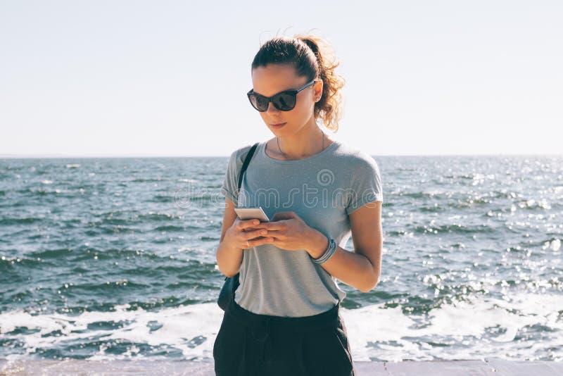Moderne junge Frau in der Sonnenbrillestellung lizenzfreie stockfotos