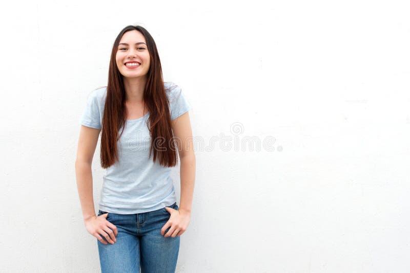 Moderne junge Frau, die auf weißem Hintergrund lächelt stockbild