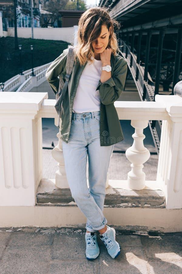 Moderne junge Frau, die nahe Stadtbrücke aufwirft lizenzfreie stockbilder