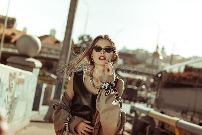 Moderne junge Frau, die stilvolle Kleidung und Sonnenbrille trägt stockfotos