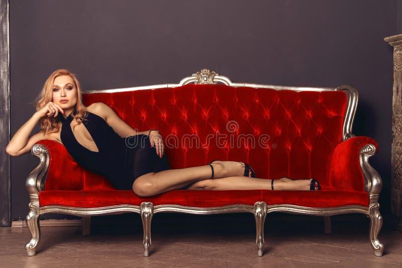 Moderne junge Frau in einem schwarzen Abendkleid liegt auf einer roten antiken Couch lizenzfreies stockbild