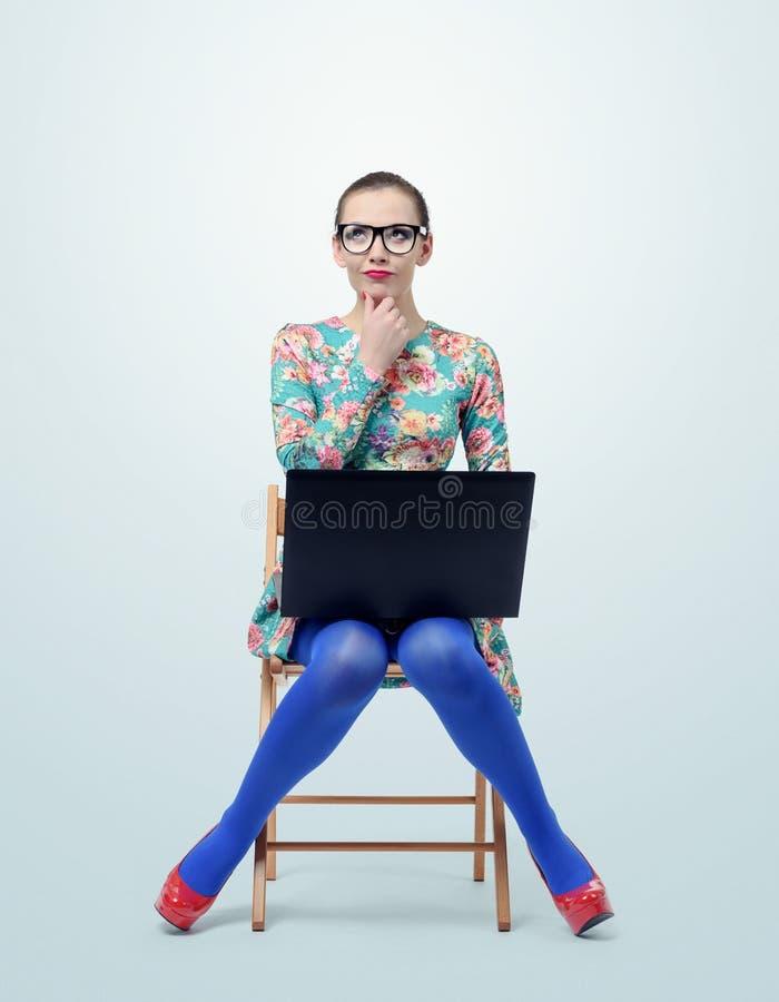 Moderne junge Frau im Kleid und in Gläsern, die auf Stuhl mit einem Laptop sitzen stockfotografie