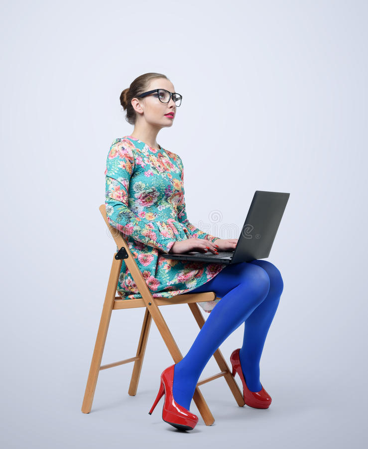 Moderne junge Frau im Kleid und in Gläsern, die auf Stuhl mit einem Laptop sitzen stockfotos