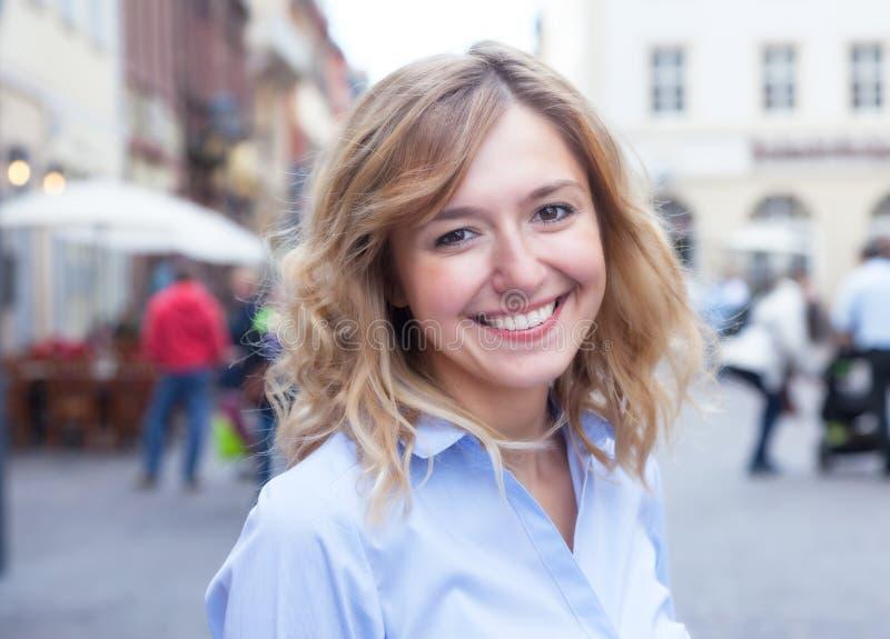 Moderne junge Frau mit dem gelockten blonden Haar in der Stadt lizenzfreies stockbild