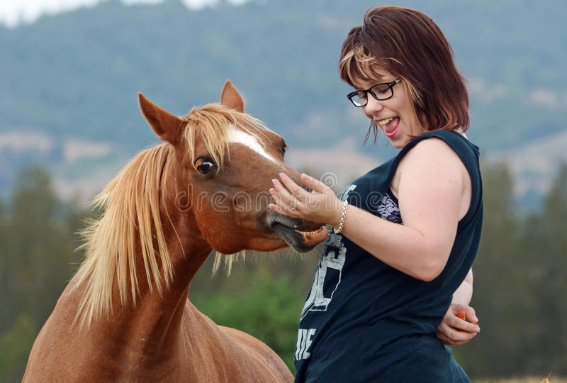 Moderne junge Frau u. Pony, die im Land lachen lizenzfreie stockfotografie
