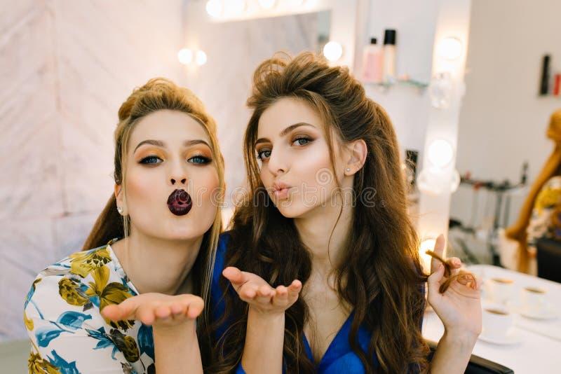 Moderne junge Frauen des Portr?ts, die einen Kuss zur Kamera im Friseursalon schicken Spa?, Luxusmake-up, bereitend zu haben vor stockfoto