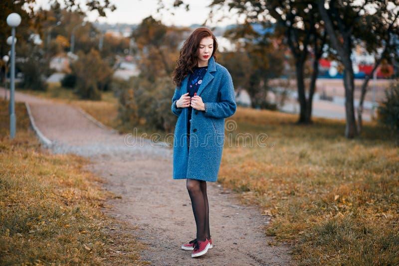 Moderne junge gelockte Frau im Herbst in lächelndem tragendem blauem Mantel des Parks und in den roten Turnschuhen stockbild