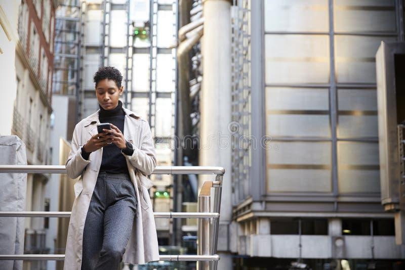Moderne junge Stellung der schwarzen Frau in der Stadt, die auf einer Handschiene unter Verwendung ihres Smartphone, niedriger Wi lizenzfreies stockfoto