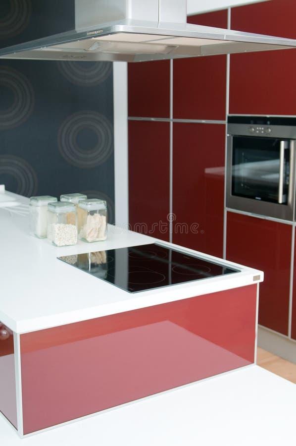 Moderne Küche mit Ofen in den roten Tönen stockbild