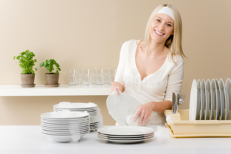 Moderne Küche - waschende Teller der glücklichen Frau stockfotos