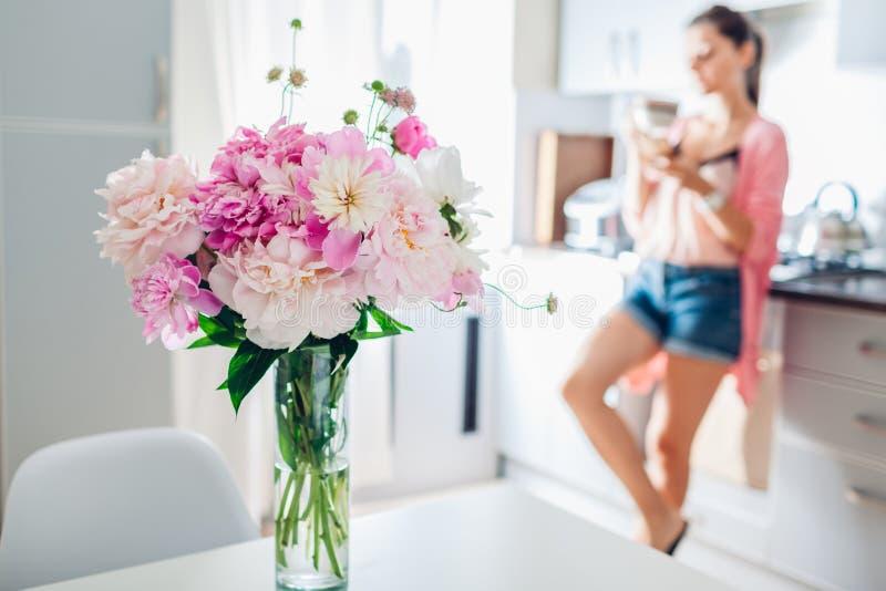 Moderne K?che verziert mit rosa Pfingstrosen Frau, die Kaffee trinkt und unter Verwendung des Telefons sich entspannt Wiedergabe  lizenzfreie stockbilder