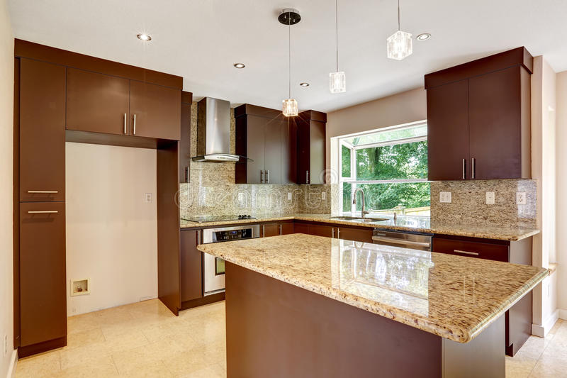 Moderne keukenruimte met steen bruine kabinetten en glanzend graniet royalty-vrije stock foto's