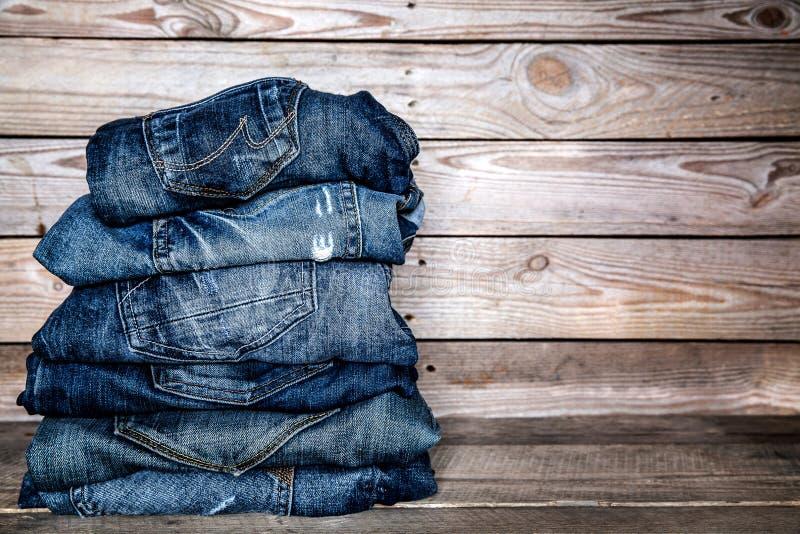 Moderne Kleidung Stapel von Jeans auf einem hölzernen Hintergrund lizenzfreies stockfoto