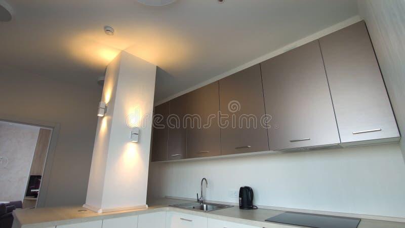 Moderne kleine ruimte met keukengebied en houten vloer Modern modieus keukenbinnenland royalty-vrije stock foto's