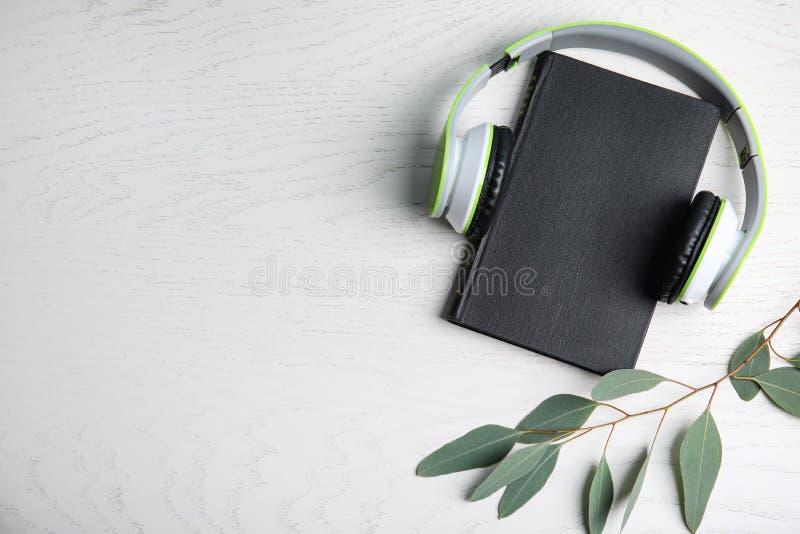 Moderne Kopfhörer mit Hardcover-Bücher auf hölzernem Hintergrund, Topansicht Textbereich lizenzfreie stockbilder