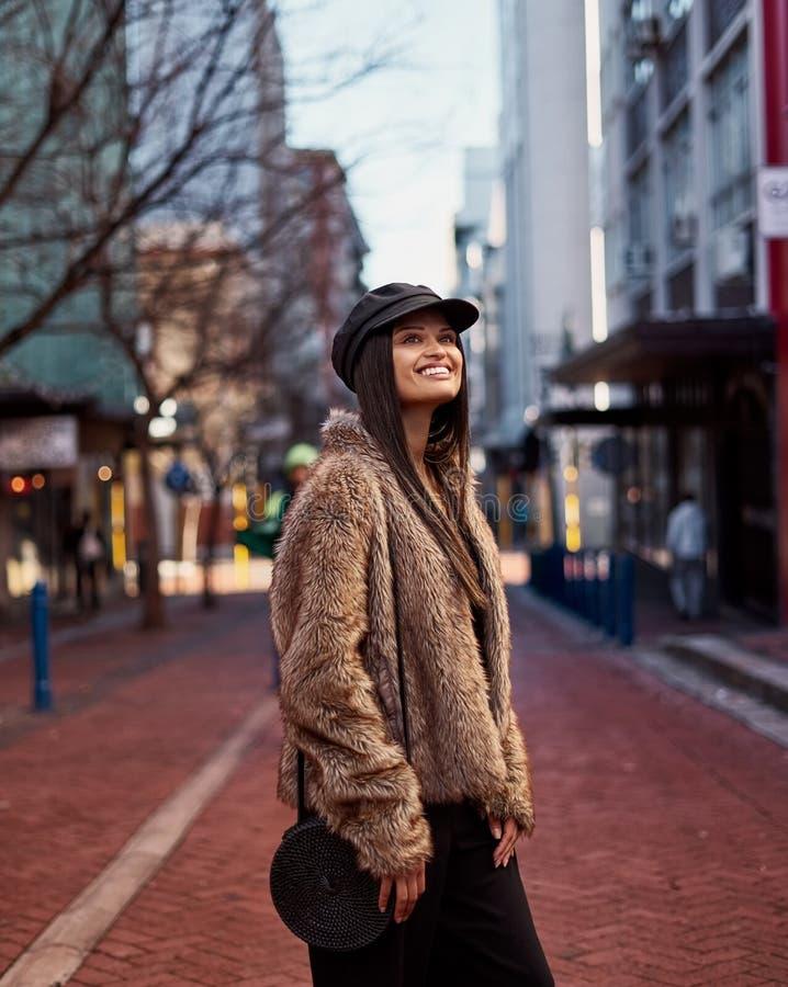 Moderne lächelnde junge weibliche tragende Schultertasche, die an steht stockbilder