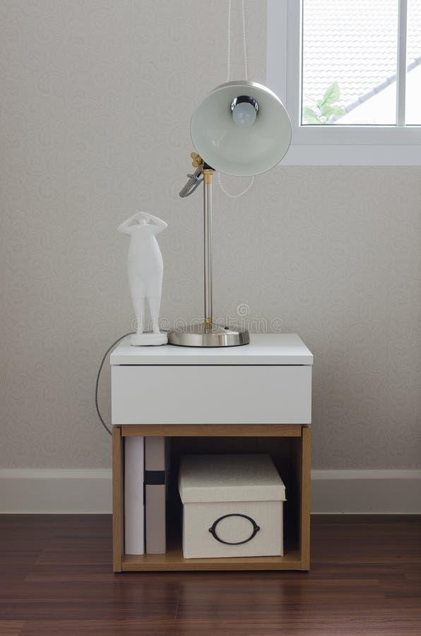 Moderne Lampe auf weißer Tabelle im Schlafzimmer lizenzfreies stockbild