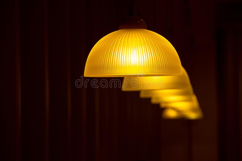 Moderne Lampen, die von der Decke auf einem dunklen Hintergrund hängen Das Konzept des Entwurfes eines gemütlichen Cafés oder der stockfoto