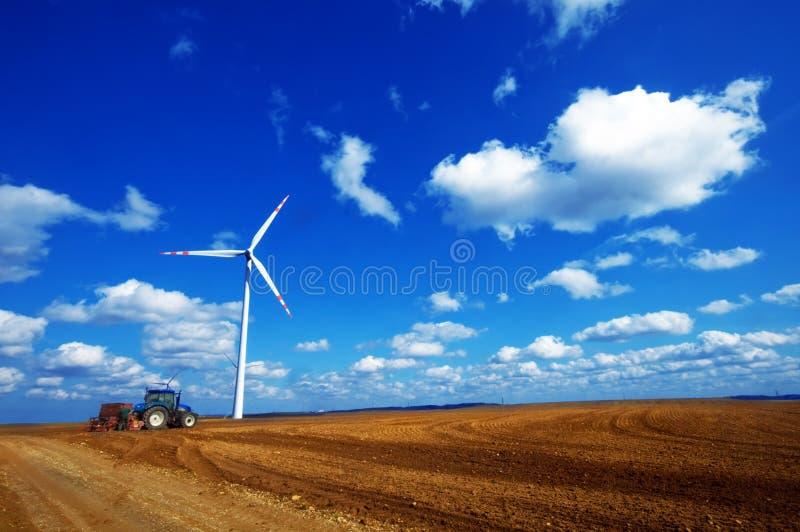 Moderne Landwirtschaft, Windturbine und Traktor stockfotografie