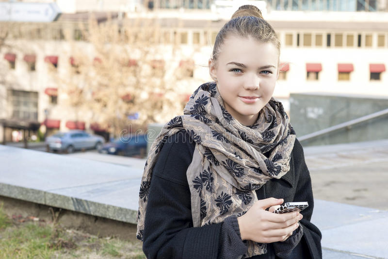Moderne Lebensstil-Konzepte: Modisches Jugendlich-Mädchen, das Mobiltelefon verwendet lizenzfreies stockfoto