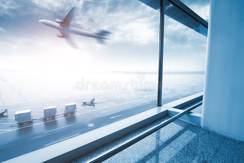 Moderne luchthavenscène van het onduidelijke beeld van de passagiersmotie met buiten venster stock fotografie