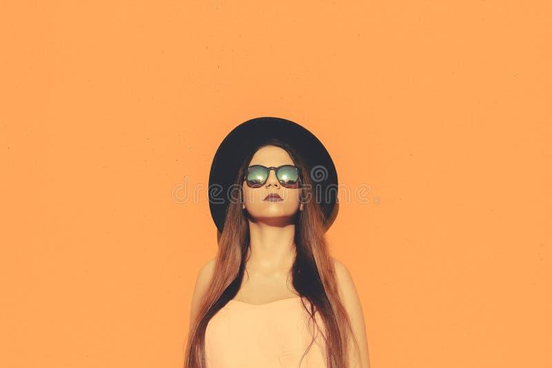 Moderne Mädchenstellung, die moderne Sonnenbrille und schwarzen Hut mit einem Normallack als Hintergrund trägt stockfotografie