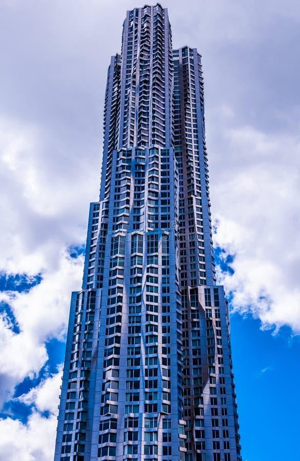Moderne metaal glanzende wolkenkrabber met golvende vormvoorgevel en bewolkte blauwe hemel stock afbeeldingen