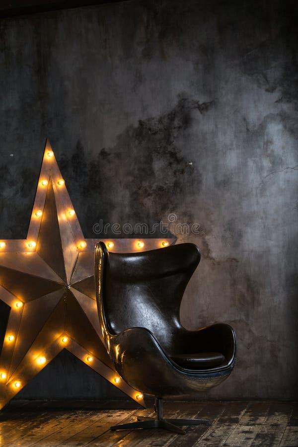 Moderne metaalstoel in een donkere ruimte stock afbeeldingen