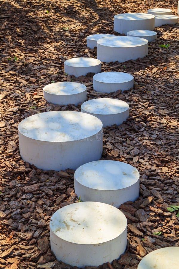 moderne minimalistische weg van ronde stenen in het Park die ter plaatse met mulch bedekte schors van bomen leiden stock fotografie