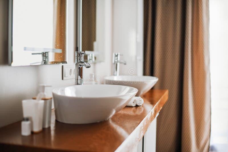 Moderne modieuze wasbakken met chroomkranen Eigentijds binnenland Luxelevensstijl Houten Textuur stock foto's
