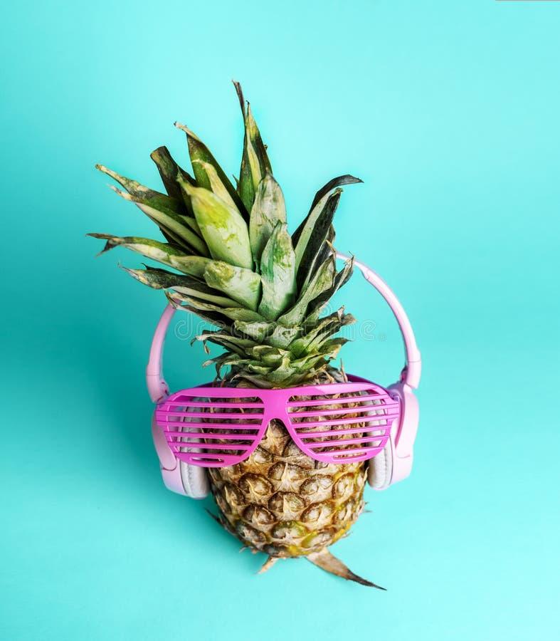 Moderne modische Ananasfrucht mit Kopfhörern und Sonnenbrillen hören Musik über hellem cyan-blauem Pastellhintergrund lizenzfreies stockfoto