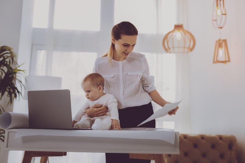 Moderne moeder die haar leuk babymeisje voor laptop plaatsen terwijl het werken stock foto
